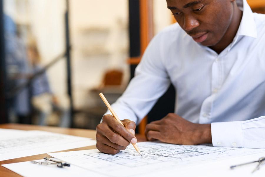 Surety Bonds - Business Man Working on Building Plans