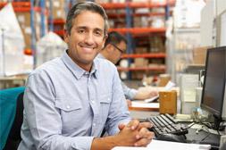 man at computer in warehouse