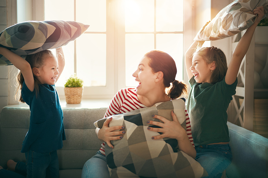 Blog - Mother and Children Having Fun During a Pillow Fight with Sunlight Shining Through Window in the Background