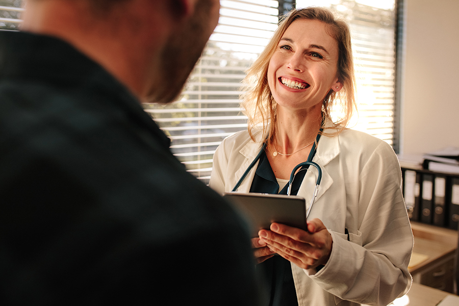 Employee Benefits - A Happy Doctor Smiling and Giving a Positive Update to Her Patient From Her Office
