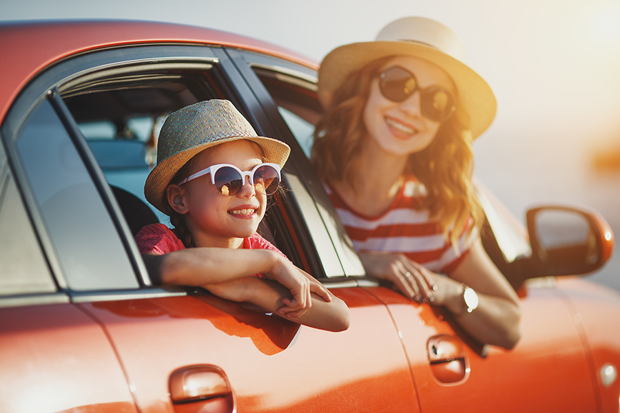 Personal Insurance - Two Children Laughing and Looking Outside of a Red Car at Sunset